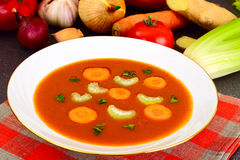 Carrot Tomato Soup in white Plate. Behind lie on the soup ingred Stock Photography