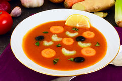 Carrot Tomato Soup in white Plate. Behind lie on the soup ingred Royalty Free Stock Image