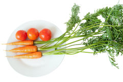 Carrot and tomato on white plate Stock Photography