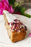 Carrot vegan cake with coconut icing and dried wild rose petals. (rosa rugosa royalty free stock photography