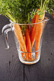 Carrot vegetable juice in glass jug. On wood background Stock Photo