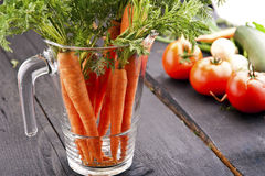Carrot vegetable juice in glass jug. On wood background Stock Image