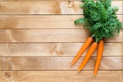 Carrot vegetable with leaves on the wooden background. Stock Photo