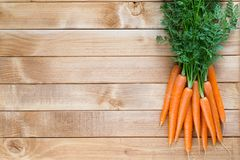 Carrot vegetable with leaves on the wooden background. Royalty Free Stock Photography