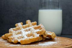 Two carrot waffles sprinkled with powdered sugar on a wooden board. Homemade waffles on a wooden plate. In the background is a gla stock photo