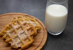 Carrot waffles with powdered sugar on a wooden board with a glass of milk. Perfect healthy breakfast stock photo