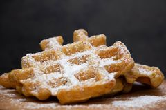 Two carrot waffles sprinkled with powdered sugar on a wooden board. Homemade waffles on a wooden board royalty free stock images