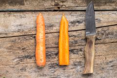 Carrot whole and cut in half with knife on wood background Royalty Free Stock Photos