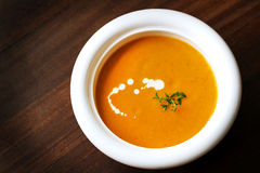 Carrot and yam creamy soup with cream and thyme Royalty Free Stock Image