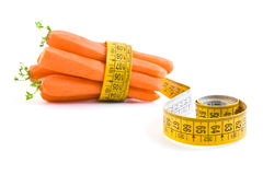 Carrot and yellow measuring tape. On the white background Royalty Free Stock Images