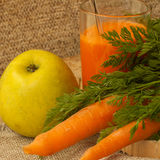 Carrots, apple and freshly squeezed carrot juice in a glass Royalty Free Stock Photos