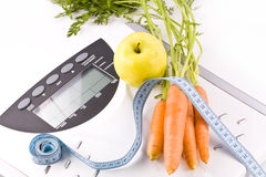 Carrots, apple and measuring objects Stock Photos