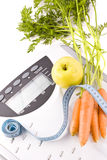 Carrots, apple and measuring objects Royalty Free Stock Photo