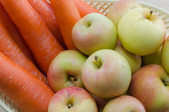 Carrots and apples in a basket. Stock Photo