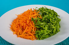 Carrots and arugula. A white plate with a salad of carrots and arugula on a blue-green background royalty free stock photo