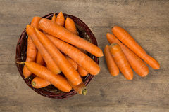 Carrots. Basket of carrots on wood Stock Images