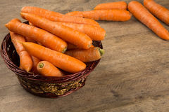 Carrots. Basket of carrots on wood Stock Image