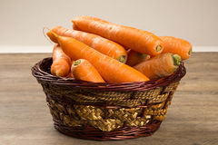 Carrots. Basket of carrots on wood stock photography