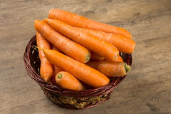Carrots. Basket of carrots on wood Stock Photo