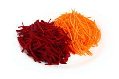 Carrots and beets sliced julienne. Plague and beets cut into sticks and put on a plate Royalty Free Stock Photo