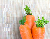 Carrots on brown fabric background. Carrots on a de-focus brown synthetic fabric background Stock Photography