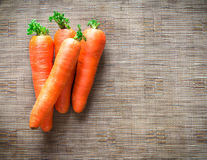 Carrots on brown fabric background. Carrots on a brown synthetic fabric background Royalty Free Stock Images