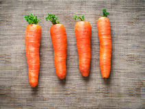 Carrots on brown fabric background. Carrots on a brown synthetic fabric background Royalty Free Stock Image