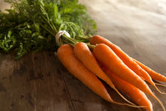 Carrots bunch. With leaves on wooden background royalty free stock photography