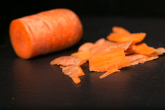 Carrots and carrot cleanings on a black board Stock Images
