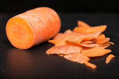 Carrots and carrot cleanings on a black board. Close up, small depth of sharpness Stock Image