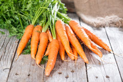 Carrots (close-up shot). Some fresh Carrots on wooden background (close-up shot Stock Photography
