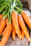 Carrots (close-up shot). Some fresh Carrots on wooden background (close-up shot Stock Photos