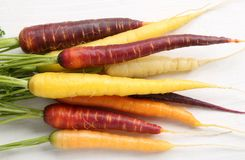 Carrots. Colorful carrots on a wooden white background Stock Photography