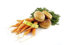 Carrots and Doughnut with Tape Measure Royalty Free Stock Images