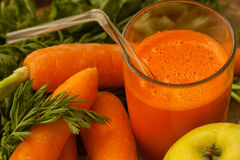 Carrots and freshly squeezed carrot juice in a glass Royalty Free Stock Images