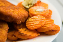 Carrots, fried meat. Carrot slices close-up with pieces of fried soy meat substitute royalty free stock image