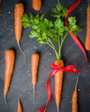 Carrots with a gift red ribbon, green tops on a black background. View from above Stock Image