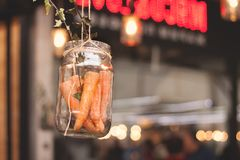 Carrots in a glass jar hanging on a rope. Stock Images