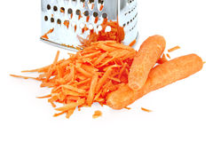 Carrots grated and whole with grater Royalty Free Stock Image
