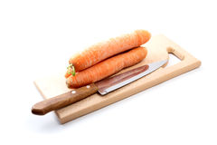 Carrots  and  knife on a chopping board Stock Image
