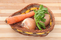 Carrots, onions and dill in a basket Stock Photography