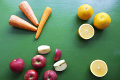 Carrots, orange and apple - mix of fruits. On the wood background Stock Image