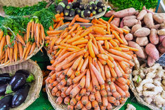 Carrots and other vegetables. In baskets for sale at a market Royalty Free Stock Photography