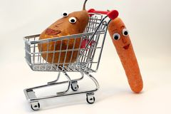 Carrots pushes the shopping cart with a PEAR with eyes Royalty Free Stock Images