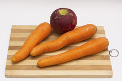 Carrots and red radish on cutting board. With isolated white texture Royalty Free Stock Image