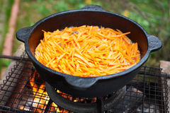 Carrots are roasted on surface of cauldron Stock Photography