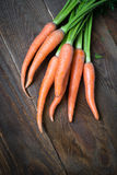 Carrots. Some fresh carrots at the wooden table Royalty Free Stock Photo
