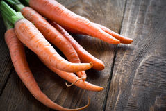 Carrots. Some fresh carrots at the wooden table Royalty Free Stock Photos