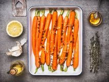 Carrots with thyme, garlic, lemon and honey on baking tray , cooking preparation with ingredients, top view. Healthy root vegetabl Stock Photo