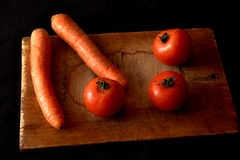 Carrots and tomatoes on an old chopping board Stock Images